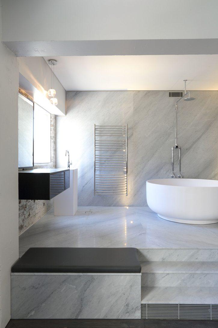 white marble bathroom design with large white bathtub