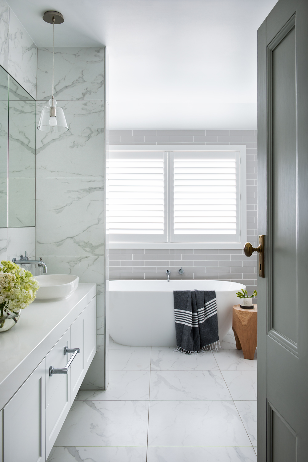 white marble bathroom design with grey tiling and white bathtub