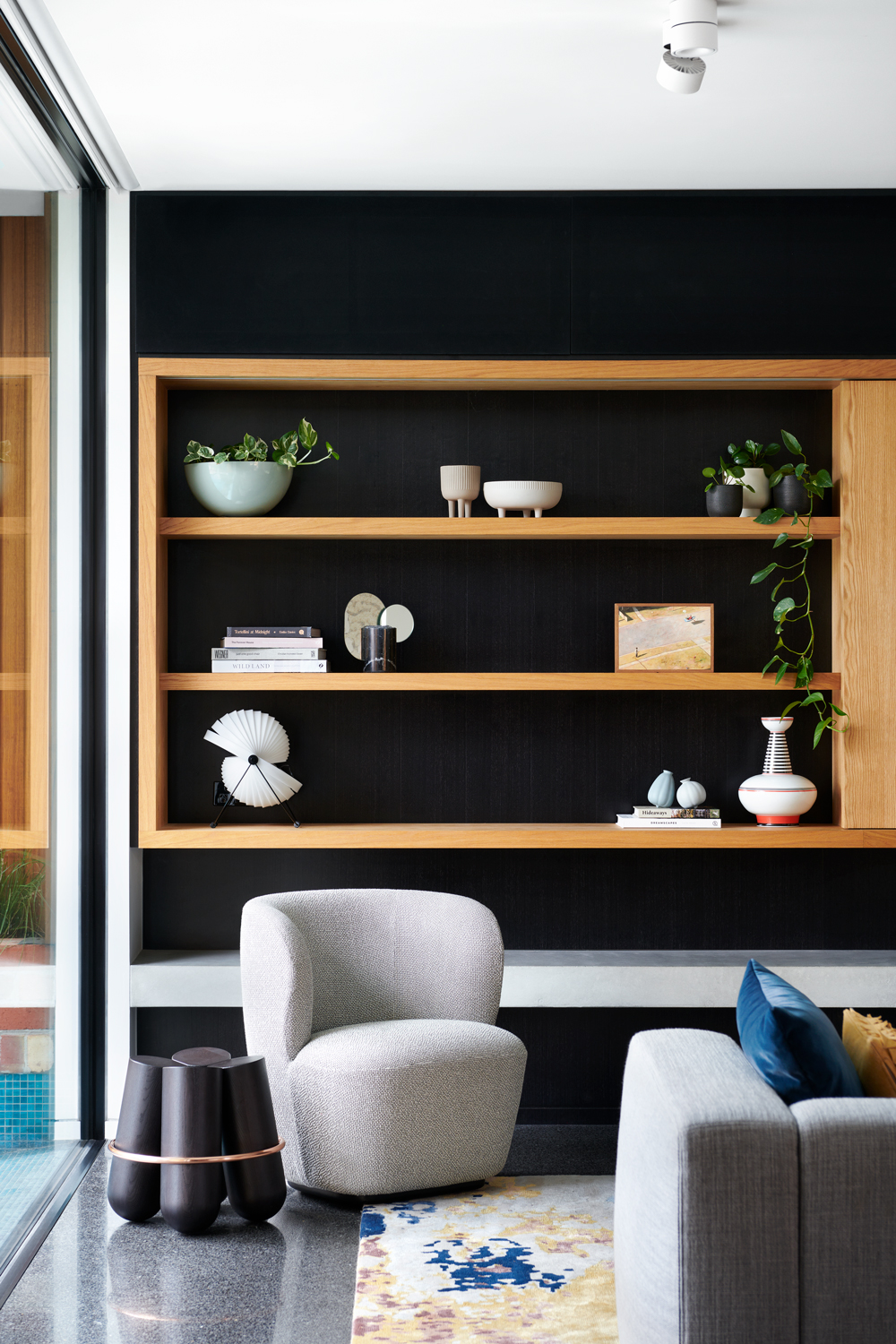 An open-plan lounge with open shelves made of natural timber.